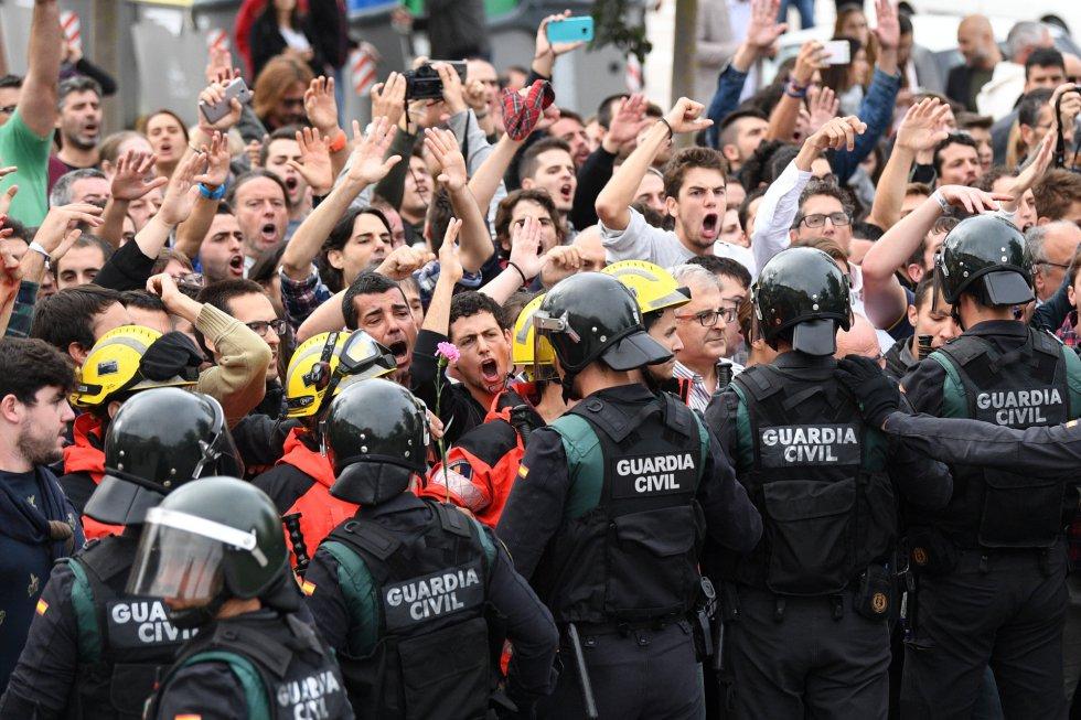 Un grupo de bomberos se coloca entre manifestantes y Guardia Civil fuera de una mesa de votación en San Julià de Ramis, Gerona.