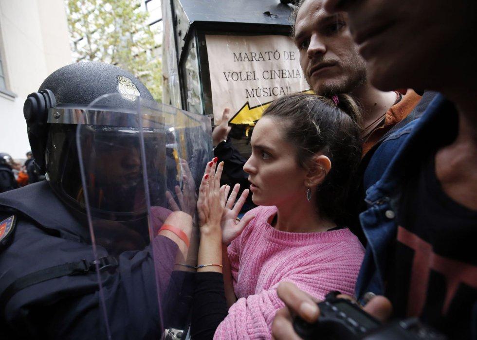 La policía evita con sus escudos que la gente se acerque a una mesa de votación en Barcelona.