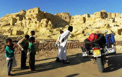 Niños curiosos frente a la vieja ciudadela de Siwa, Egipto, mítico oasis del Oráculo