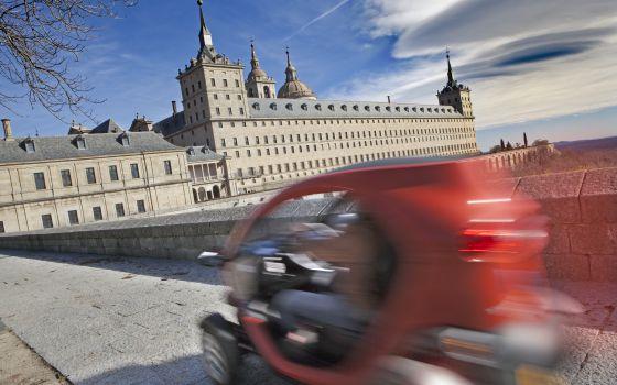 Un coche eléctrico con la fachada del monasterio de El Escorial al fondo.