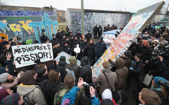 Manifestantes paralizan el derribo, ya comenzado, de un tramo del Muro de Berlín e intentan recolocar una réplica exacta de la parte demolida en el hueco abierto por los obreros.