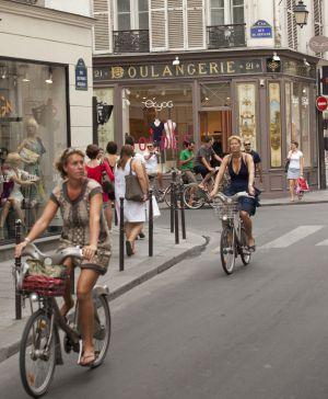 Dos ciclistas con bicis del sistema Vélib', en la Rue des Francs Bourgeois de París.