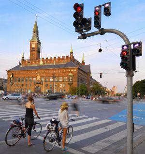 Dos chicas esperan su turno para circular en el centro de Copenhague. Al fondo, el edificio del ayuntamiento de la capital danesa.