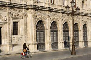 Una ciclista pasa por la Plaza de San Francisco de Sevilla, con una bici ´de la red pública de alquiler Sevici.