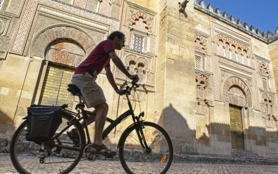 Un ciclista a su paso por la fachada oriental de la mezquita de Córdoba.