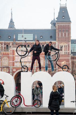Jóvenes con bicicletas sobre las icónicas letras que representan a la ciudad junto a la plaza de los museos.