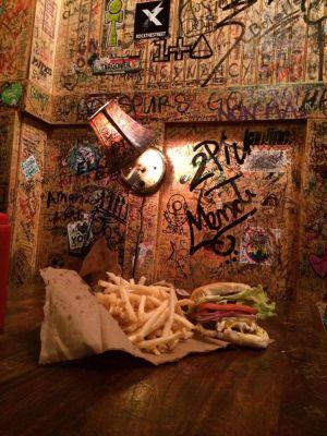 Hamburguesa y patatas fritas entre grafitis y garabatos en Burger Joint, en el vestíbulo del hotel Le Parker Meridien, en Nueva York.