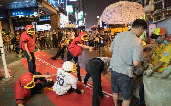 El grupo de teatro Prototype Paradise realizando una de sus 'performances' junto a un camión de basura en Taipéi, en Taiwán.