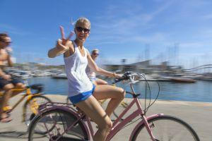 Una joven pasea en bicicleta por el paseo marítimo de Barcelona.