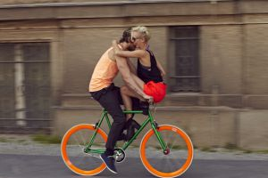 Una pareja monta en una colorida bici por las calles de Berlín.