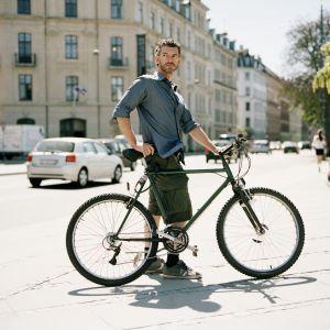Un hombre lleva su bicicleta por Copenhague.