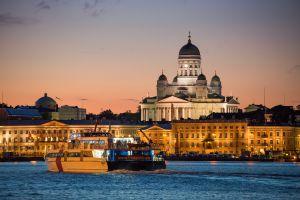 Un catamarán con la catedral de Helsinki al fondo.