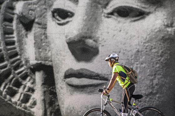 Ciclista delante de un vitromosaico con la imagen de la Dama de Elche en la plaza del Parque.