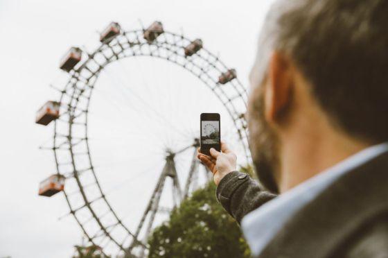 Un hombre toma una fotografía de la noria de Prater.