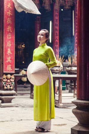 Una joven ataviada con el 'lao dai', la vestimenta tradicional vietnamita, en un templo de Saigón.