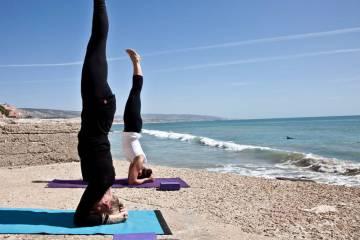 Sesión de yoga en la playa organizada por Yoga & Surf Retreats Vila Mandala, en Marruecos.