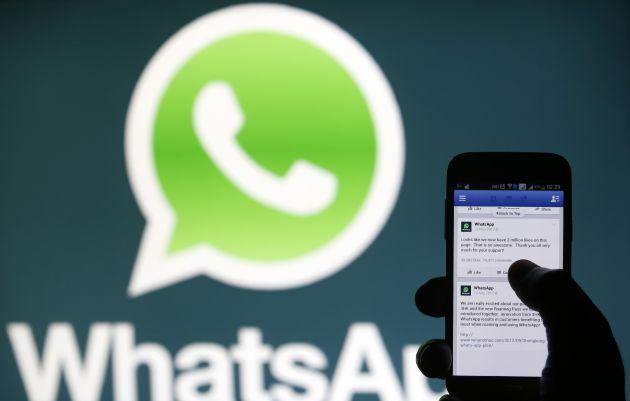 Un usuario de móvil frente al logo de WhatsApp