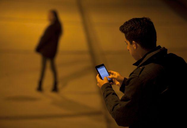 Un joven envía un mensaje con su móvil.