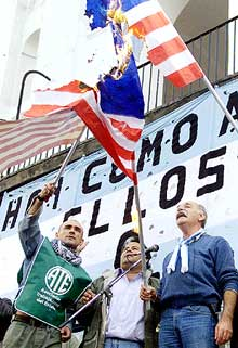 Trabajadores estatales argentinos quemaron ayer banderas americanas durante una manifestación en Buenos Aires.