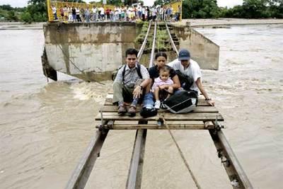 En la imagen, varias personas son evacuadas tras quedar seriamente dañado el puente de Ciudad Hidalgo (Chiapas), en la frontera de México con Guatemala.