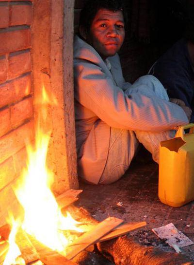 Un indígena paraguayo se refugia del frío en una plaza de Asunción.