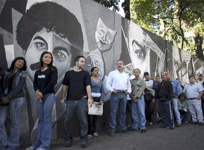 Varios ciudadanos hacen cola para votar en Caracas.