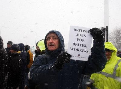 Un huelguista muestra una pancarta a favor del trabajo para los británicos en la refinería de Lindsey.