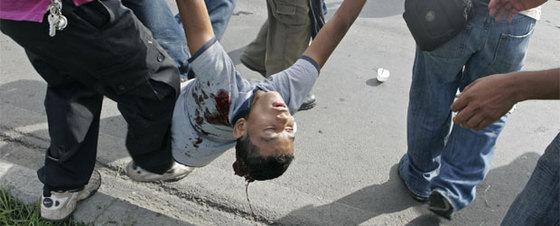 Partidarios de Zelaya tratan de socorrer a Isis Obed Murillo, de 19 años, alcanzado en la nuca por un disparo.