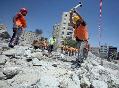 Empleados palestinos de la Agencia de la ONU para los Refugiados trabajan en la reconstrucción de Gaza.