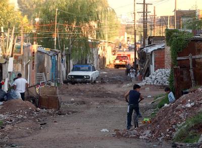 Unos niños juegan entre escombros y basura, en una zona de chabolas de Buenos Aires.