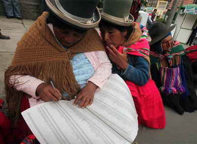 Indígenas concentrados ante la Corte Nacional Electoral comprueban sus nombres en las listas para las elecciones del domingo.