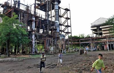 Un grupo de niños juega ante la fábrica causante del accidente, ya abandonada, el pasado mes de noviembre