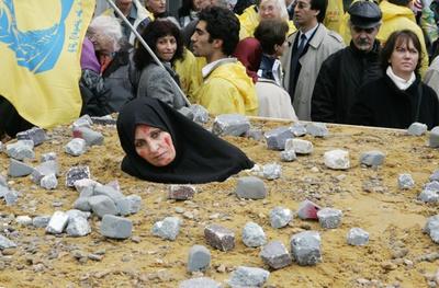 Una mujer iraní simula una lapidación en Bruselas en señal de protesta.