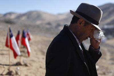 Ramón Ávalo, de 81 años, se seca las lágrimas al ver las banderas con los nombres de sus dos nietos, atrapados en la mina San José.