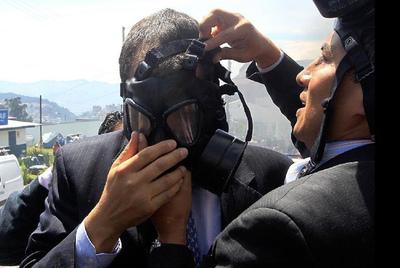 Un escolta ayuda al presidente Correa a colocarse una máscara antigás durante la revuelta de los policías.
