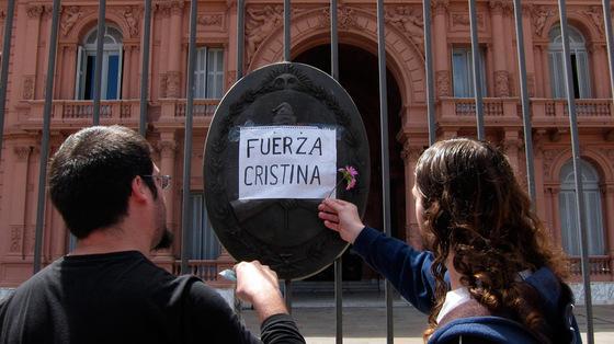 Dos hombres dejan una flor en la Casa Rosada, en Buenos Aires.