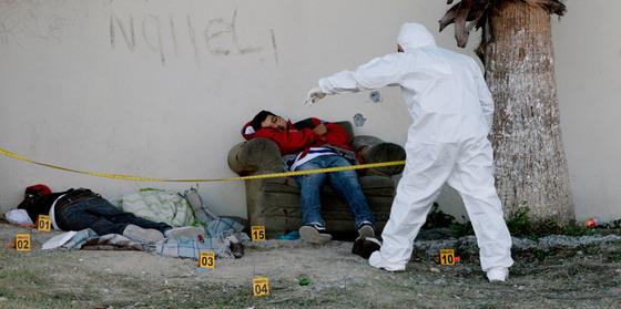 Forenses examinan  los cuerpos de dos jóvenes asesinados en Apodaca, a las afueras de Monterrey, México, el pasado 1 de diciembre.