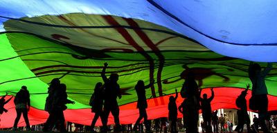 Un grupo de manifestantes enarbolan una enorme bandera mapuche durante una protesta el pasado septiembre en la ciudad de Concepción.