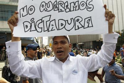 Un hombre muestra un cartel de rechazo a la Ley Habilitante en una protesta a las puertas de la Asamblea venezolana durante la votación de la medida.