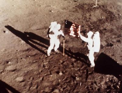 Los astronautas Neil Armstrong y Edwin E. Aldrin colocan la bandera de los Estados Unidos sobre la superficie de la Luna.