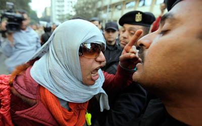 Una manifestante se encara a un policía antidisturbios que bloquea el paso a una manifestación del sindicato de periodistas.