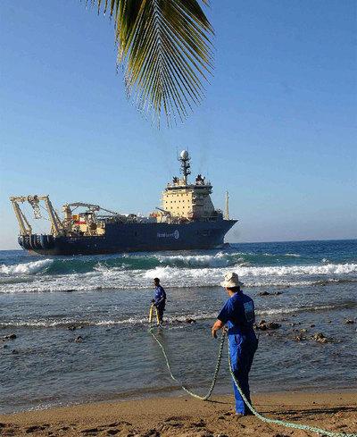 Obreros cubanos arrastran un cable submarino de fibra óptica en la playa de Siboney.