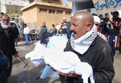 Un hombre carga con partes de un cadáver a las puertas de un hospital de Bengasi, la segunda ciudad libia. Según el recuento de la ONG Human Rights Watch, al menos 233 personas han fallecido en la represión de las protestas contra Gadafi.