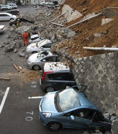 Coches aplastados por un muro derrumbado en un aparcamiento en la ciudad de Mito, en la provincia de Ibaraki, después del terremoto que sacudió Japón hoy viernes