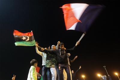 Los opositores a Gadafi agitan en Bengasi su bandera tricolor y la bandera francesa tras la aprobación de la resolución de la ONU que autoriza el uso de la fuerza contra Gadafi.