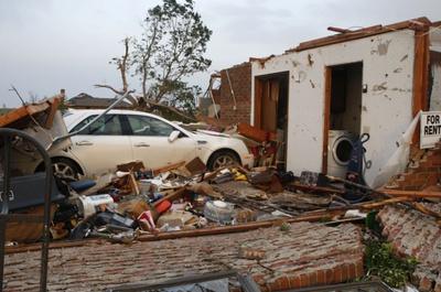 Un coche empotrado contra un garaje tras el paso del tornado en Piedmont, en Oklahoma.