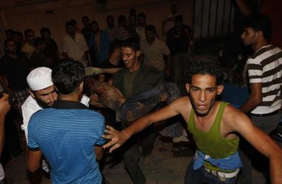 Los palestinos llevan a los heridos al tras un bombardeo israelí en la ciudad Rafha, al sur de la franja de Gaza.