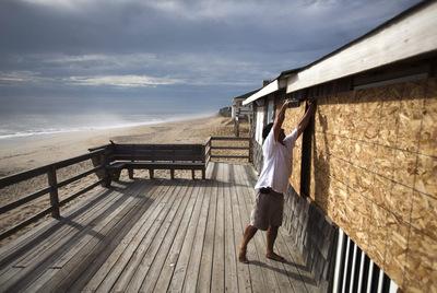 Un hombre coloca tablones de madera para proteger las ventanas de una casa en Kitty Hawk, Carolina del Norte, unas horas antes de que el huracán Irene toque tierra en esa región de EE UU