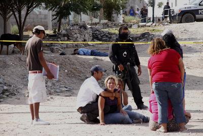 Los familiares de cuatro jóvenes tiroteados el domingo en Ciudad Juárez llegan al lugar del asesinato, acordonado por la policía.