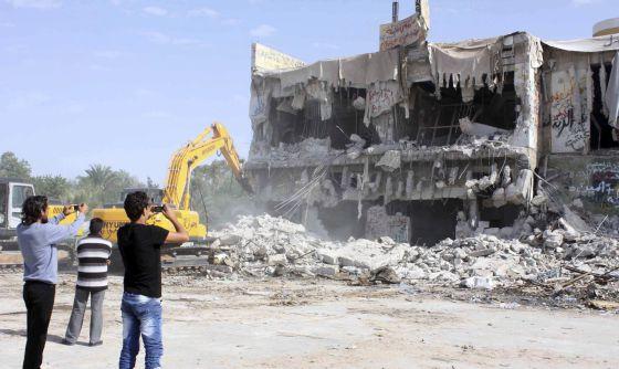 Varios libios toman fotografías de la destrucción de la casa del fallecido líder libio Muamar al Gadafi.